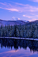 Trees and mountains with new snow and reflection in Nancy Greene Lake at sunset, with cirrus intortus clouds, BC.