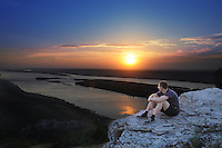 Man watching sunset in Russian National Park Samaraskaya Luka sitting on a rock