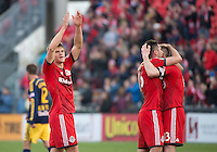 Toronto, Ontario - May 17, 2014: Toronto FC defender Nick Hagglund #17 and Toronto FC defender Bradley Orr #16 and Toronto FC defender Steven Caldwell #13 celebrate the win in  a game between the New York Red Bulls and Toronto FC at BMO Field. Toronto FC won 2-0.