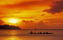 Guam, Micronesia: outrigger canoe paddlers at sunset at Tumon Bay resort area.