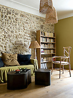 In this bedroom a wall painted olive green with a matching linen-covered sofa accentuate the tones of the ancient stone