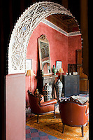 An ornate carved archway leading into the living room of The Red Suite at the Riad Dar Darma in Marrakech