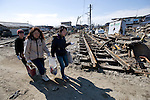 Having reclaimed some of their possessions from destroyed homes, a mother and her children walk past the shattered railway station in Tona, Miyagi Prefecture, Japan on  25 March 20011. .Photographer: Robert Gilhooly