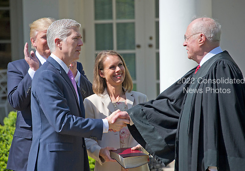 Associate Justice of the United States Supreme Court Neil Gorsuch, left, shakes hands with Associate Justice Anthony Kennedy, right, after taking the Oath of Office in the Rose Garden of the White House in Washington, DC on Monday, April 10, 2017. Gorsuch's wife Louise holds the Bible.<br /> Credit: Ron Sachs / CNP<br /> (RESTRICTION: NO New York or New Jersey Newspapers or newspapers within a 75 mile radius of New York City)