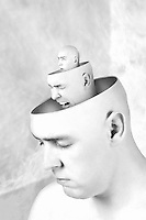 Two heads with facial expressions inside of another head revealing the persons hidden feelings.
