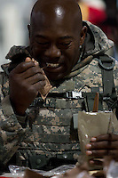 Specialist Curtis Murphy, of McDonough, Georgia, tears open a cheese spread packet from a MRE (Meal, Ready to Eat) during a media visit day at Camp Atterbury, Indiana on Wednesday, June 3, 2009. The Georgia Army National Guard's 48th Brigade, 148th Brigade Support Battalion, trained in an attack and medical evacuation scenario after lunch. The brigade's upcoming overseas mission is to train the Afghan National Army and Police forces.