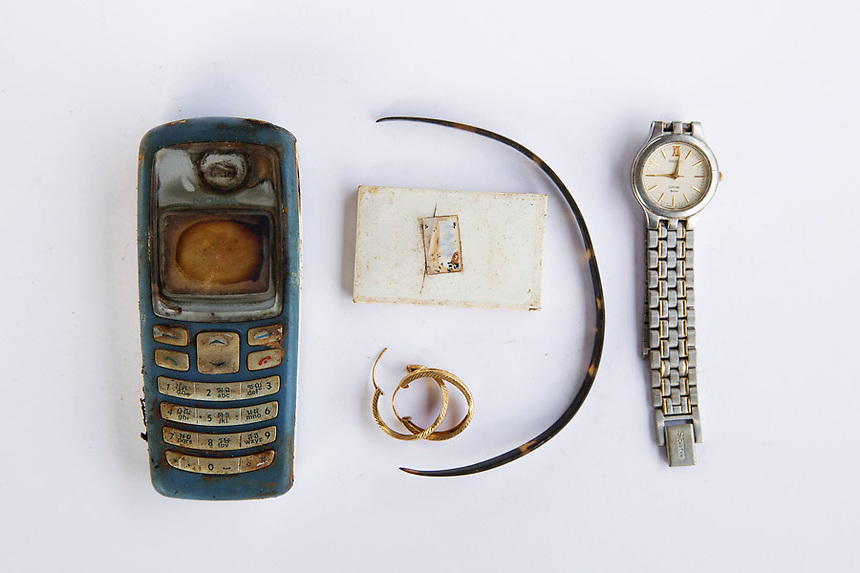 Personal possessions of 2004 tsunami victims are arranged to be photographed outside a police station in Takua Pa in Phang Nga province December 19, 2014. Ten years after the deadliest tsunami in recorded history, and years after it was handed over to them by teams who worked on the process of identification, police opened a container which was filled with documents and possessions of tsunami victims after being asked by Reuters for permission to film the contents of the container. Thailand prepares to mark the tenth anniversary of 2004 tsunami, the deadliest on the record, that killed at least 226,000 people in 13 Asian and African countries. In Thailand, over 5300 people were killed, including several thousand foreign tourists, when the waves swamped six coastal provinces, turning some of the world's most beautiful beaches into mass graves. REUTERS/Damir Sagolj (THAILAND)