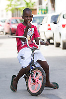 A kid plays with his bike in the street