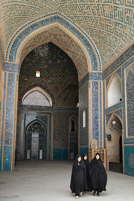Three Iranian women walk out from the Jameh Moqsue of Yazd. Located in the old part of the city, its tiled entrance portal is one of the tallest in Iran. This mosque is also crowned by a pair of minarets.