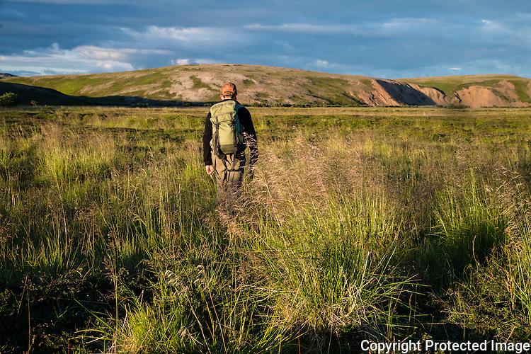 Mann går over grasslette høyt oppe i Komagelva. ---- Man crossing grassy plains in the upper part of Komagelva.