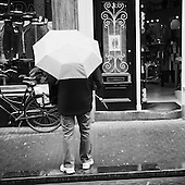 Man standing undar an umbrella in front of a shopping window in down town Amsterdam