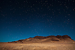 Crown Butte in Central Montana extends above the prairie towards a blue sky filled with stars.