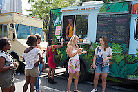 """Hungry attendees to the AfroPunk Festival in Commodore Barry Park in Brooklyn in New York on Sunday, August 26, 2012 enjoy juice from Green Pirate truck the food truck festival. The festival in the neighborhood of Fort Greene bills itself as the """"other black experience"""" and blends the black punk and hardcore punk scenes. There is also a diverse aspect combining other minority groups, all dressed in their fashionable punk ensembles. (© Richard B. Levine)"""