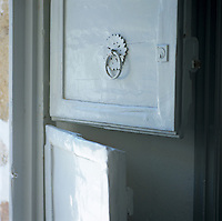 A rustic stable-style door and knocker painted white herald the entrance to the house