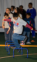 A Local student jumps over a hurdle during a US Soccer Foundation clinic held at City Center in Washington, DC.