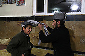 BIARA, IRAQ: Abit al-Jabar (20) teaches a younger student, Anas, how to tie his jamana, or headscarf...The Biara Madrassa--a religious school--is located high up in the mountainous Kurdish Hawraman region that makes up the Iran/Iraq border. Before 2003 the region was home to a fundamentalist Islamic group called Ansar al-Islam who used the school as a base. The Unites States military attacked the area and the madrassa numerous times during the 2003 invasion, finally pushing Ansar al-Islam out...Today the madrassa is home to 48 male students from all across Kurdish Iraq. The students leave their families and immerse themselves in their studies and the daily life of Koranic students...Photo by Besaran Tofiq