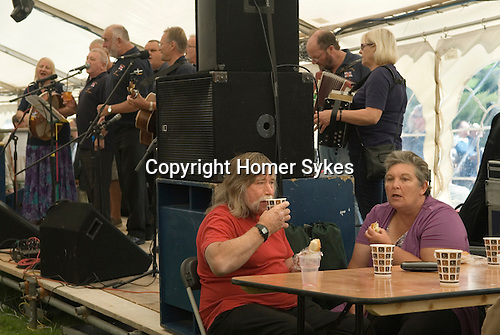 Widecomb Fair, Widecombe in the Moor, Dartmoor, Devon Uk.   The beer tent with couple. The folk band is Friggn Riggin.