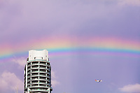 A rainbow and an aircraft pass near a Miami condo building.