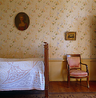 Side view of a simple French bed and an Empire chair against a wall of floral wallpaper