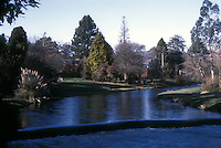 Overview with river, waterfall, trees, plantings, grasses, lawn, at Mount Usher Gardens in County Wicklow, Ireland, in February - cool blue cold weather