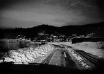 Nuclear winter in Fukushima, Prefecture: Night falls on a narrow row in an evacuated village in Iitate-mura.  Villages in the extended nuclear evacuation zone still have electric power, evident in the street lamps, but residents may be forbidden from living in their homes for many years or even decades.  Iitate-mura was contaminated by wind-driven radioactive fall-out from the Fukushima Dai Ichi nuclear power plant.  Iitate-mura sits in an area that annual ambient radiation rates are estimated to be over 20 millisieverts in most areas and others are at over 50 millisieverts annually, the latter of which may indicate that decontamination may take decades.