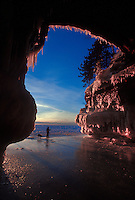 A snowshoer and her dog explore the ice-covered sea caves of Lake Superior at Squaw Point in Apostle Islands National Lakeshore near Bayfield, Wis.