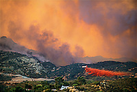 870000029 fiire fighting aircraft drops fire retardant on a hillside and isolated homes in the hills above chatsworth in the northwest section of the san fernando valley near the simi hills in los angeles county california