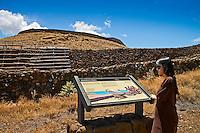 A female visitor looking at the Mailekini Heiau informational sign at Pu'ukohola Heiau National Historic Site, Kawaihae, Kohala, Big Island.