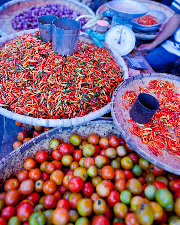 Several kinds of peppers, tomatos, and other spices and vegetables are displayed for sale at one vendor's stand in the market, in Bitung, North Sulawesi, Indonesia.