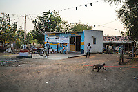 A monkey runs across the grounds as customers gather at the iJal water station to buy drinking water in Gorikathapalli, a remote village in Warangal, Telangana, India, on 22nd March 2015. Safe Water Network works with local communities that live beyond the water pipeline to establish sustainable and reliable water treatment stations within their villages to provide potable and safe water to the communities at a nominal cost. Photo by Suzanne Lee/Panos Pictures for Safe Water Network