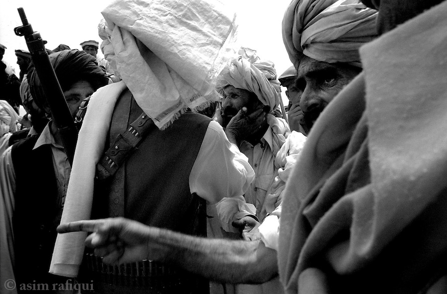 azam warsak, south wazisitan, pakistan 2004: men from a tribal lashkar attempt to calm a hysterical family member whose house is being torched by the lashkar.  traditional homes may have many families living within them.  the suspicion that even one member is harboring al qaeda means the entire house is destroyed.<br />