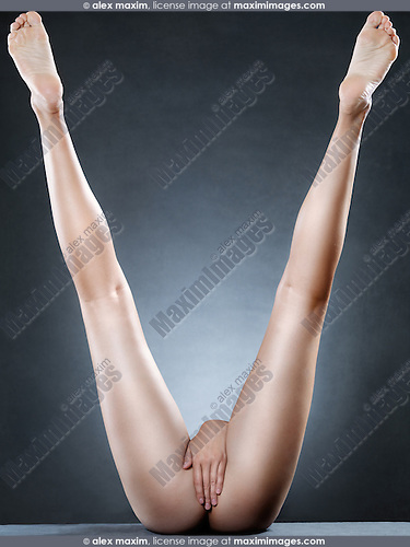 Long sexy woman legs pointing up making V shape. Artistic nude photo.