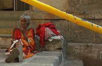 Outskirts of Mumbai, streetscene, an old women in the afternoon sun, Mumbai, India
