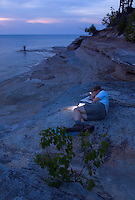 A backpacker reads by headlamp while sitting on the sandstone shoreline of Mosquito Beach in Pictured Rocks National Lakeshore near Munising, Mich.