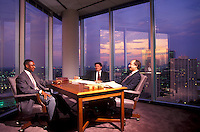 Stock photo of executives meeting in a corner office with a city view