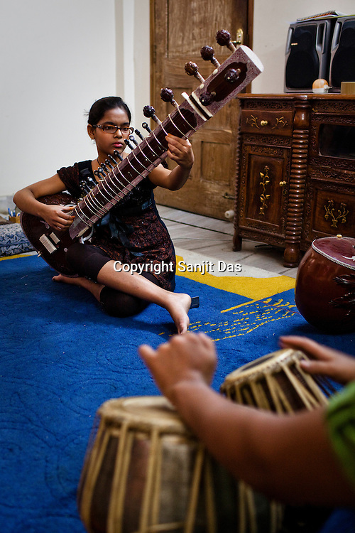 12 year old Aayushi Dwedi plays sitar in a class in a music class at the Academy of Indian Classical Music in Varanasi in Uttar Pradesh, India. Photograph: Sanjit Das/Panos