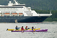 Kayakers paddle along side Holland America cruise ship in Sitka Sound, coastal town of Sitka along the Alaska Inside Passage. A favorite stop for tourist.