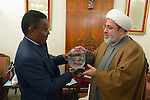 The Rev. Frank Chikane (left), moderator of the Commission of the Churches on International Affairs of the World Council of Churches, receives a memento from Yusef El-Nasar, a Shia Muslim leader, during the visit of an international ecumenical delegation to Baghdad, Iraq, on January 21, 2017. The encounter took place at St Gregory the Illuminator Armenian Orthodox Church. The memento shows images of Muslim troops helping place crosses on Christian churches following the defeat of the Islamic State group in Iraq.