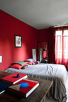 The bedroom has been painted pillarbox red and has matching sheer curtains pulled across the window