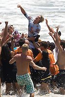 American Brett Simpson raises his arms in victory while being carried ashore after defeating South African Jordy Smith in the final heat during the 2010 US Open of Surfing in Huntington Beach, California on August 8, 2010.