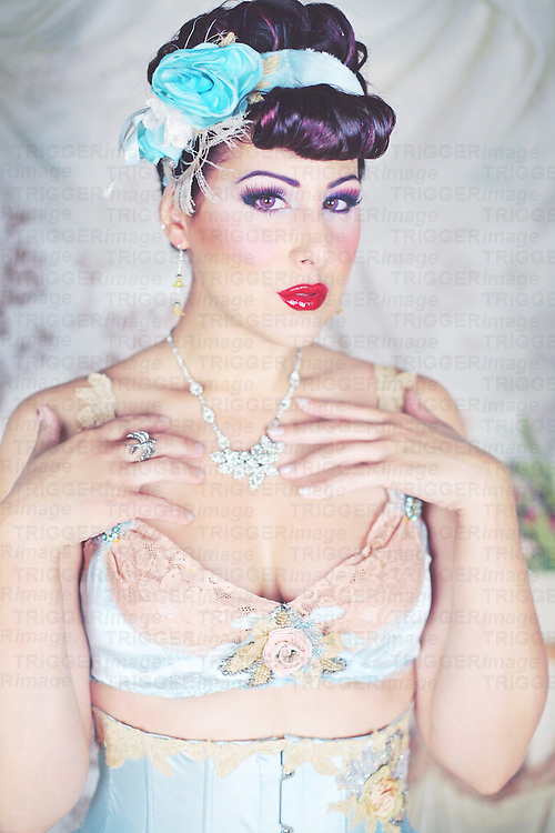 A beautiful young woman with dark hair, dressed in fancy vintage lingerie with expensive, classy jewelry