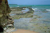 Sandstone cliffs and rocks emerging from the sea at low tide at Praia do Morro, Barra do Camaragibe, Atlantic coast, Alagoas, Brazil