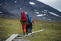 Hikers walk on wooden planks between Alesjaure and Tjäktja, Kungsleden trail, Lapland, Sweden