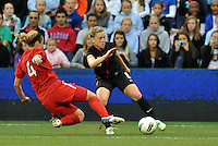 USWNT midfielder Amy Rodriguez (8) evades the tackle of Canada's Carmelina Moscato.