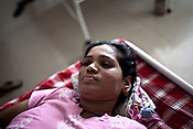 A surrogate mother lying in bed at the Akanksha Infertility and IVF Clinic in Anand, Gujarat, India. The centre has become the most popular clinic for outsourcing pregnancies by western couples.