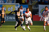 Freddy Adu (11) of the Philadelphia Union is chased by Daniel Woolard (21) of DC United. DC United defeated Philadelphia Union 1-0 during a Major League Soccer (MLS) match at PPL Park in Chester, PA, on June 16, 2012.