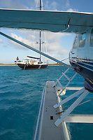 Exumas, Bahamas 2006 - 115 foot Sloop 'Tenacous'  and a Cessna Caravan seaplane tied to the stern in the shallow waters off the Exumas chain of islands in the Bahamas.