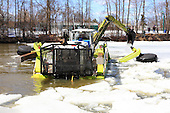 The back of an amphibious excavator breaking the ice cover on the L'Assomption river in Joliette, Quebec