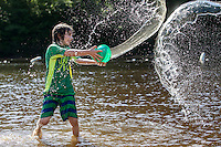 Koa Klose, 8, of Northampton, MA, tosses water during a water fight with a friend at Musante Beach in Leeds, MA.