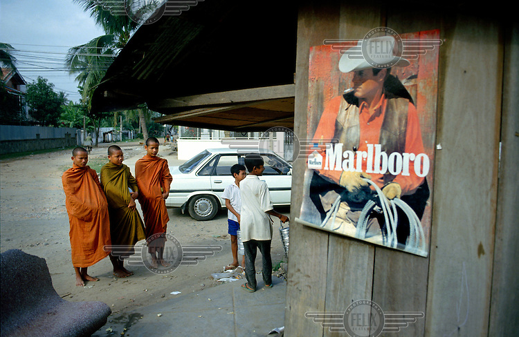 Marlboro cowboy looks on as young monks beg for alms at a street corner stall.